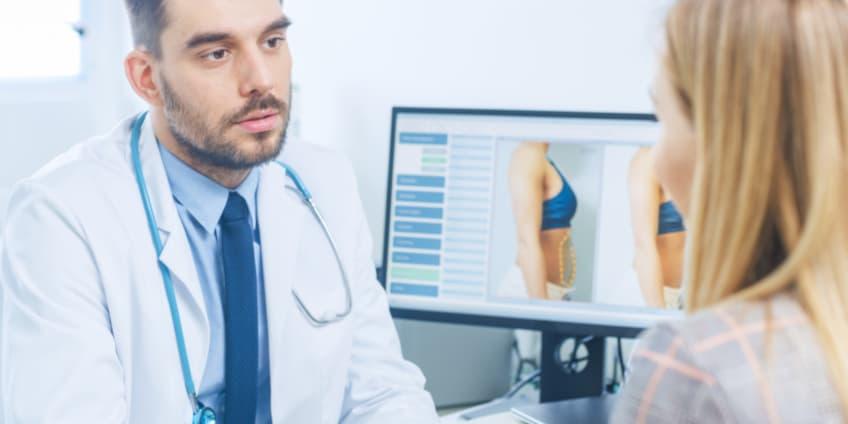 طبيب يحاور مريضة حول أضرار عملية شفط الدهون بعد الجراحة