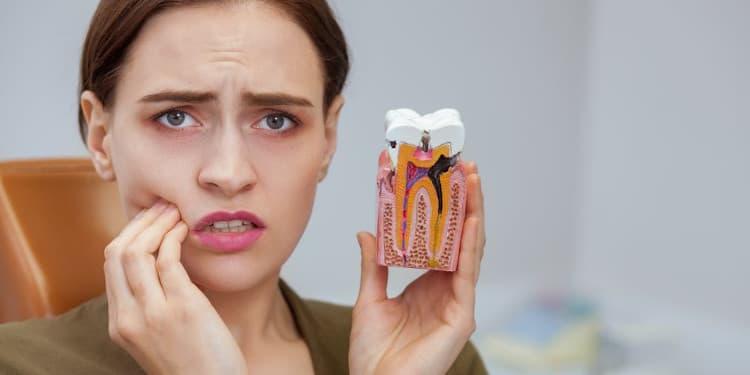 امرأة تؤدي إنطباع عن الألم الناتج عن تسوس الأسنان وهو ما يتطلب علاج